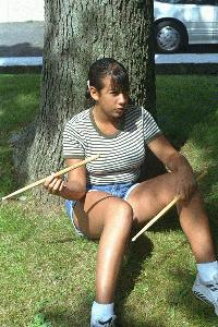 Dana twirling a drumstick in front of her house.